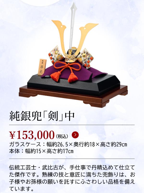 純銀兜「剣」中 ¥153,000(税込) ガラスケース:幅約26.5×奥行約18×高さ約29cm 本体:幅約15×高さ約17cm 伝統工芸士・武比古が、手仕事で丹精込めて仕立てた傑作です。熟練の技と意匠に満ちた兜飾りは、お子様やお孫様の願いを託すにふさわしい品格を備えています。